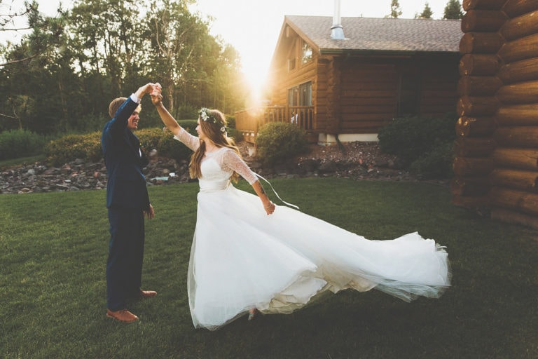Bride and groom dancing in front of a cabin