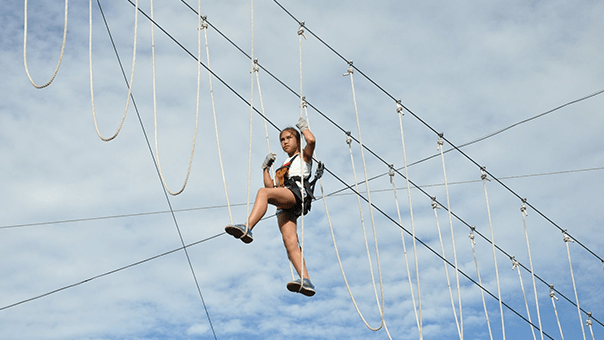 Woman crossing a rope bridge